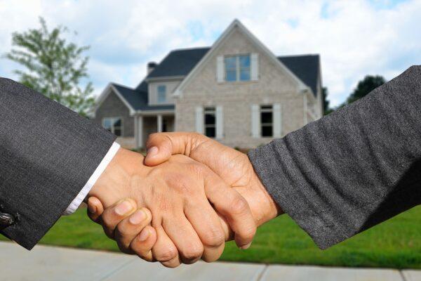 manos que se estrechan sinónimo de cliente satisfecho tras visita de software inmobiliario.
