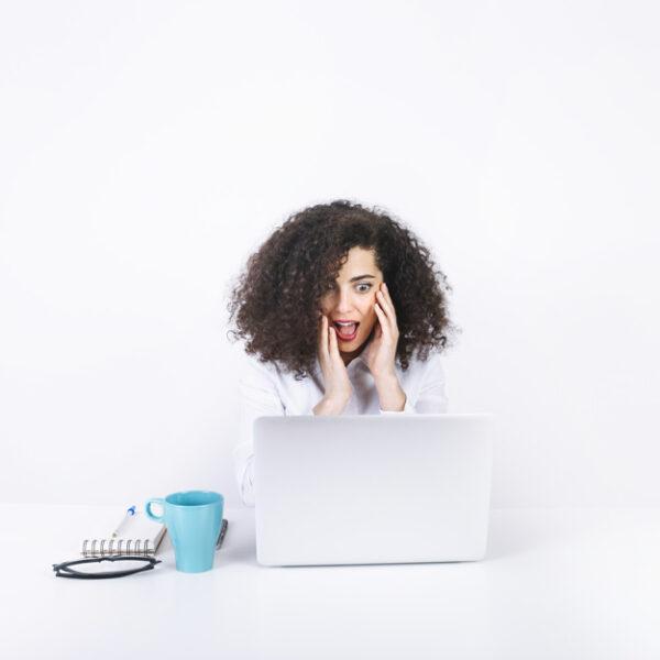 mujer sorprendida trabajando con CRM inmobiliario