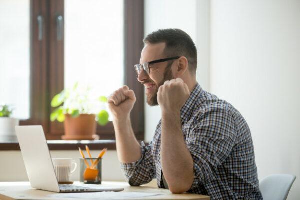 agente inmobiliario trabaja en laptop y descubre feliz las ventajas de Wasi sobre portal inmobiliario