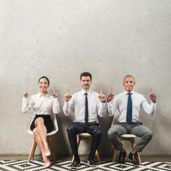 candidatos en proceso de selección a agente inmobiliario eficiente levantan dedo índice.